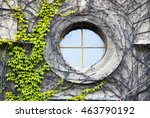 A Round Window With Ivy Wall