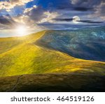 day and night composite image of winding road through large meadows on the hillside of Polonina mountain range - stock photo