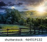 day and night composite image of wooden fence on agricultural grassy meadow with trees on hillside in high mountains at sunset - stock photo