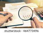 Small photo of Man hand holding magnifying glass analyzing business financial data