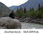 Man Sitting On A Large Rock...