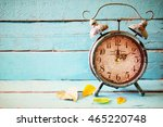 Stock photo image of autumn time change fall back concept dry leaves and vintage alarm clock on a blue rustic 465220748