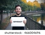 Small photo of Young man holding Advocacy sign