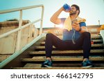Stock photo tired fitness man sweating taking a break listening to music on phone after difficult training 466142795