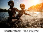 mother swim with baby in blue water at sunset; female with child bathe in lake or river and making water drops;