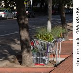 Small photo of An overturned shopping cart trolley with possessions of a homeless person on a brick walkway sidewalk of Houston Downtown. Concept for failure of society adequate systems, funding and support.
