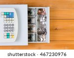Small photo of View from above on retail business cash register full of coins and bills over yellow stained wooden table