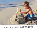 A Young Blond Boy Building Sand ...