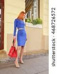 Small photo of Beautiful stylish fashion woman in bright blue top and skirt with big red lackered leather bag in hand walking through the city streets. Young woman with long red hair in blue dress.