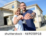 Small photo of cheerful young happy couple holding home keys in front of construction site of new house