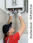 Small photo of Plumber attaches to pipe gas boiler using adjustable wrench.