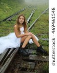 Very beautiful blonde teen girl with beautiful long legs in short shorts, black boots and a white T-shirt and white long skirt bride walking along the rails of the train.