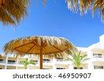 Fragment hotel building,  sun umbrella, make of reed. - stock photo