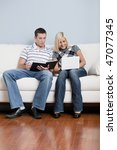Man is reading, and woman is using a laptop, as they sit side by side on a white couch. Vertical format. - stock photo