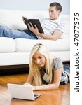 Man reads on a couch while woman stretches out on the floor with her laptop. Vertical format. - stock photo
