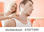 Man and woman sit on bed as woman massages man's shoulders. Horizontal format. - stock photo