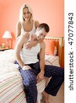 Affectionate couple in pajamas, laughing and relaxing in their bedroom. Vertical format. - stock photo
