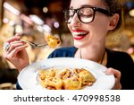 young woman eating tortellini... | Shutterstock . vector #470998538