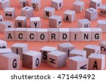 Small photo of ACCORDING word on wooden cube isolated on orange background