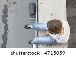 girl sit on edge of roof - stock photo
