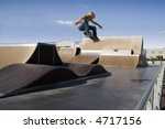 Skater doing a big air ollie in a skate park - stock photo