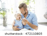 father feeding baby | Shutterstock . vector #472110805