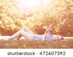 young woman lying on the grass... | Shutterstock . vector #472607392