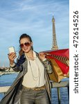 Small photo of Get your bags ready for the Paris autumn sales. smiling young fashion-monger in sunglasses with shopping bags taking selfie with smartphone in Paris, France