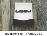 Small photo of Handle bar mustache accessorized by a black bow tie