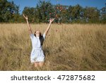 Stock photo young woman throws up rose petals woman stands on her knees and throws up rose petals her hands 472875682