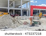 Cement mixer machine is at construction site with two wheelbarrows, tools, sand and cement bag. - stock photo