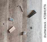 Small photo of Top view arrangement group of parts (dowel, bolt, washer, allen wrench, screw) for ready-to-assemble wooden furniture assembly on vintage ashwood board with copy space. Equipments for diy concept.
