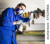 Small photo of Handyman using airbrush gun in his garage with thumb up looking at you