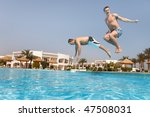 Two men jumping in swimming pool.  Low angle view from the swimming pool. - stock photo