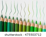 Small photo of Green pencils of different shades lying abreast and lines drawing by them on a paper.