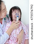 Small photo of Closeup asian child having respiratory illness helped by doctor with inhaler. Pediatrician take care girl with asthma problems making inhalation with mask at hospital. child was bronchitis and crying.