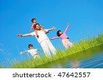 Happy family, meadow, river - stock photo