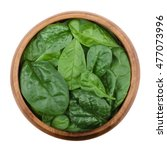 Small photo of Fresh green spinach leaves in a wooden bowl on white background. Spinacia oleracea, edible flowering plant in the family Amaranthaceae. Raw vegetable. Isolated macro food photo, close up from above.