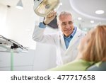senior male dentist adjust... | Shutterstock . vector #477717658