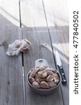 Small photo of garlic cloves in a vintage pewter bowl and a pairing knife. Weathered wood table