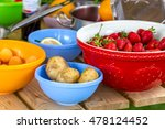 Small photo of Bowls with potatoes, apricots, strawberries, lemon for cooking with cooking utensils on a wooden table