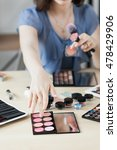 Small photo of Artist taking rouge with brush, visagiste workplace. Close-up of stylist hand on palette with pink shades bluster. Beauty, makeup, cosmetics concept