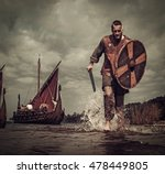 Small photo of Serious viking warrior in the attack, running along the shore with Drakkar on the background.