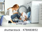 Stock photo mother a housewife with a baby engaged in laundry fold clothes into the washing machine 478483852