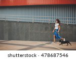 Stock photo young woman with black french bulldog puppy walking at the street 478687546