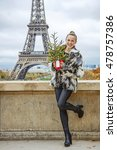 Small photo of The Party Season in Paris. Full length portrait of smiling trendy fashion-monger with Christmas tree in fur coat against Eiffel tower in Paris, France