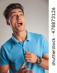 Small photo of amazed young casual man is looking up to something with mouth open