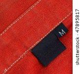 Black Tag On A Red Denim Textile