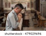 Religious Man Kneeling At The...