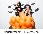 Small photo of Two cheerful young women in witch halloween costumes dancing with orange balloons over white background